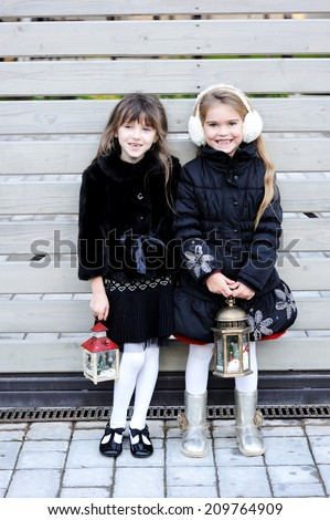 Two adorable kid girl friends in white hats and pattern black jackets has fun outdoor with Christmas lantern at the winter day - stock photo