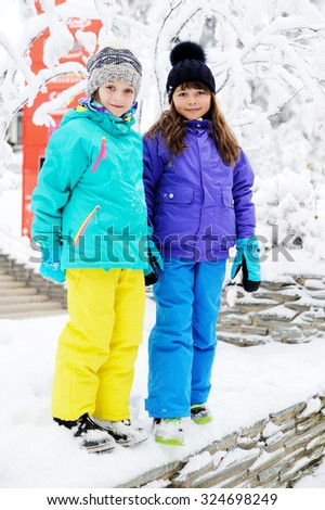 Two adorable kid girls in warm colorful clothes walking in the snowy park on beauty winter day