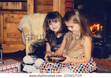 Two adorable kid girls sitting on the floor near the fireplace with christmas gifts  - stock photo