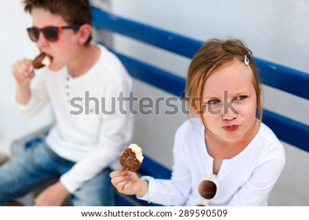 Two adorable kids eating ice cream outdoors on a hot summer day - stock photo