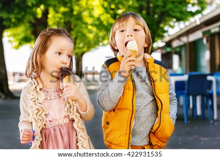 Two adorable kids, little boy and girl eating ice cream outdoors.  - stock photo