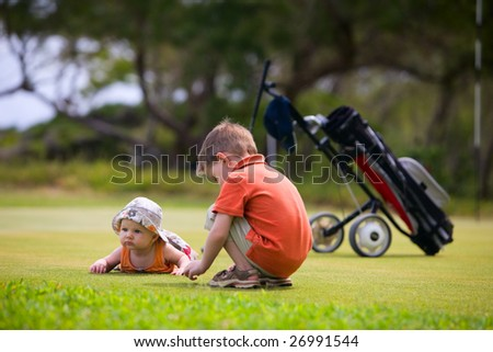 Two adorable kids playing on golf field waiting. - stock photo