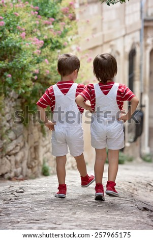 Two adorable kids, walking on the street, back to camera - stock photo
