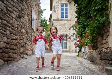 Two adorable kids, walking on the street, laughing - stock photo