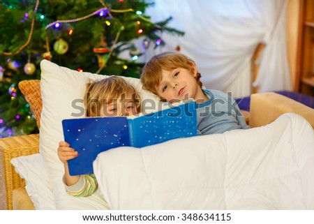 Two adorable little blond kid boys, twins reading a book together in bed near Christmas tree with lights and illumination. Happy family, two children and friends. - stock photo
