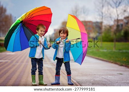 Two adorable little boys, walking in a park on a rainy day, playing and jumping, smiling, talking together, springtime - stock photo