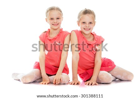 Two adorable little girl twins in pink dress sitting on the floor and smiling at the camera-Isolated on white background - stock photo