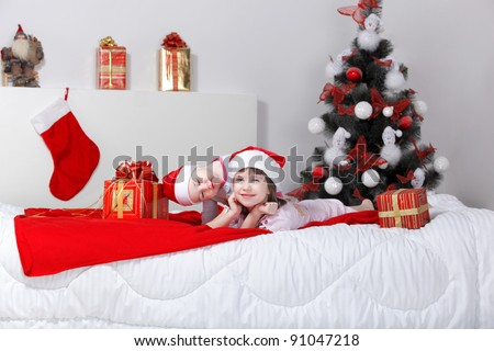 Two adorable little girls in pajamas and Christmas hats playing on bed - stock photo