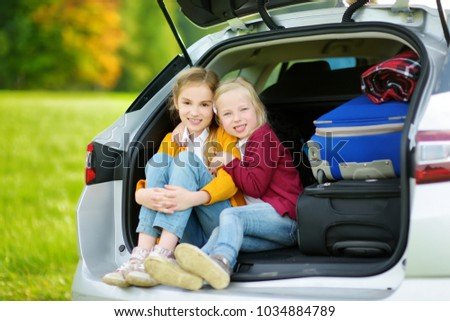 Two adorable little girls sitting in a car before going on vacations with their parents. Two kids looking forward for a road trip or travel. Family travel by car.