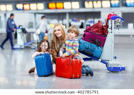 Two adorable little siblings, kid boy and girl sitting with suitcases on international airport. Young mother pushing. Brother and sister, happy family waiting for flight and going on vacations.