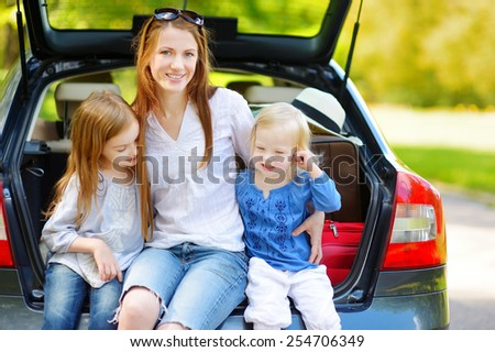 Two adorable little sisters and their mother sitting in a car just before leaving for a car vacation