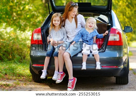 Two adorable little sisters and their mother sitting in a car just before leaving for a car vacation - stock photo