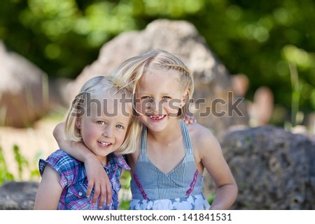 Two adorable little sisters arm in arm sitting on a rock in a park grinning happily at the camera