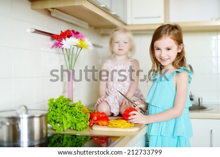 Two adorable little sisters cooking dinner in a kitchen - stock photo