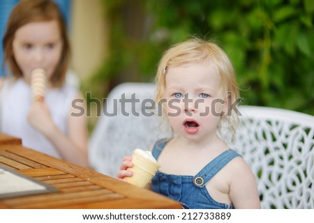 Two adorable little sisters eating an ice cream in outdoor cafe on beautiful summer day - stock photo