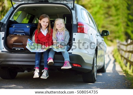 Two adorable little sisters exploring a map before going on vacations with their parents. Two kids looking forward for a road trip or travel.