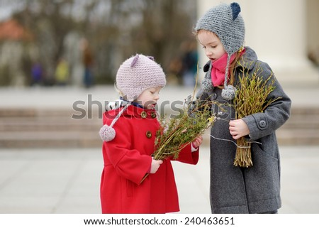 Two adorable little sisters holding willow branches and other plants as part of Easter tradition in Lithuania - stock photo