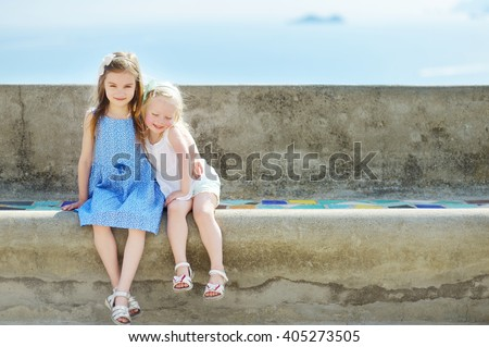 Two adorable little sisters laughing and hugging each other on warm and sunny summer day in italian town - stock photo