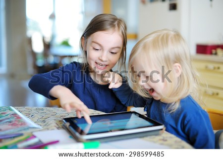 Two adorable little sisters playing with a digital tablet at home - stock photo