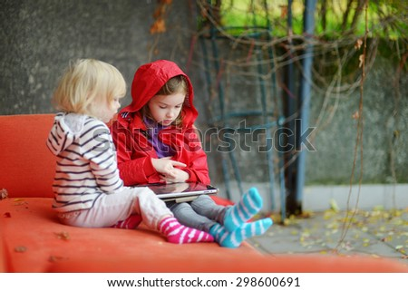 Two adorable little sisters playing with a digital tablet outdoors on autumn day - stock photo