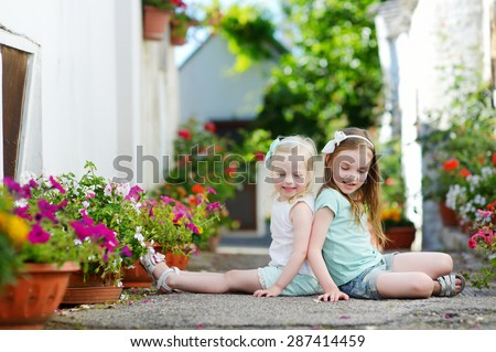 Two adorable little sisters sitting among flowers pots on warm and sunny summer day in italian town - stock photo