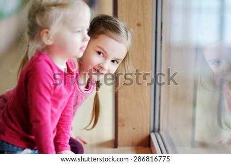 Two adorable little sisters sitting by the window at home - stock photo