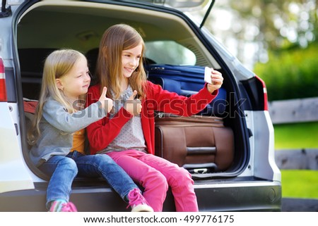 Two adorable little sisters taking photo of themself before going on vacations with their parents. Two kids sitting in a car ready to travel.