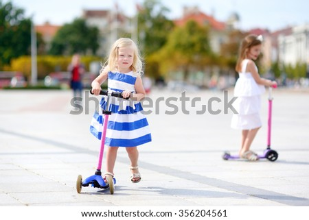 Two adorable little sisters wearing beautiful dresses riding their scooters in a summer park - stock photo