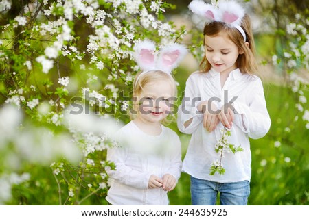 Two adorable little sisters wearing bunny ears in a spring garden on Easter day - stock photo
