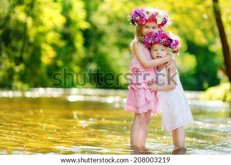 Two adorable little sisters wearing flower crowns by a river on warm and sunny summer day - stock photo