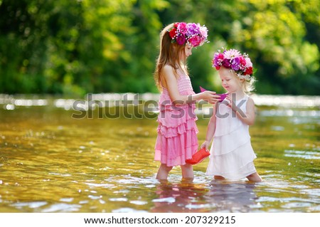 Two adorable little sisters wearing flower crowns play with paper boats by a river on warm and sunny summer day