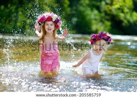 Two adorable little sisters wearing flowers crowns having fun by a river on warm and sunny summer day - stock photo