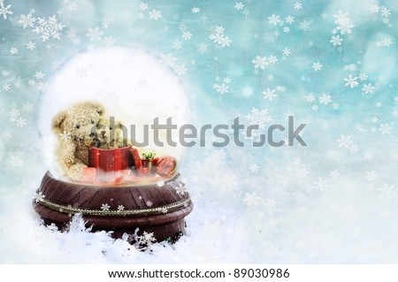 Two adorable little teddies inside of a snow globe against a blue background. - stock photo