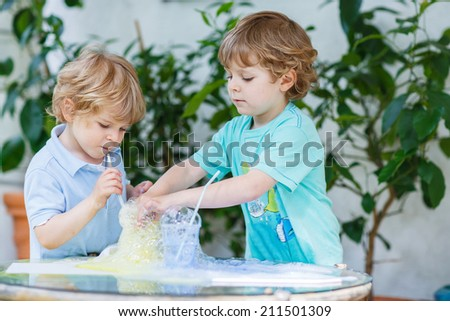 Two adorable preschool boys playing, having fun and making experiment with colorful soap bubbles and water, outdoors. - stock photo