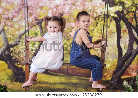 Two adorable preschoolers happily sitting on a rustic 2-person swing in a yard of blossoming trees. - stock photo