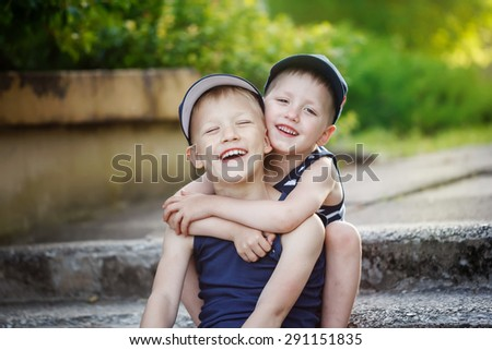 Two adorable  sibling boys hugging and having fun outdoors. Cute friends playing together on sunny warm summer day. Brother love. - stock photo