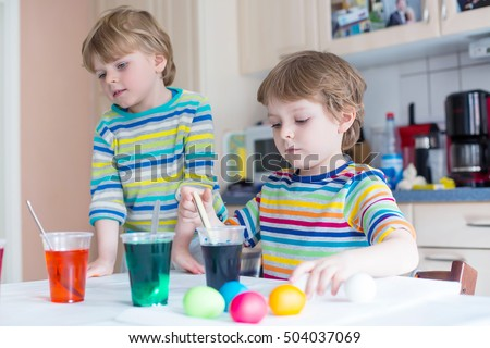 Two adorable siblings coloring eggs for Easter holiday in domestic kitchen, indoors. Children having fun and celebrating feast.