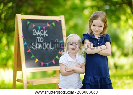 Two adorable sisters feeling unhappy about going back to school - stock photo