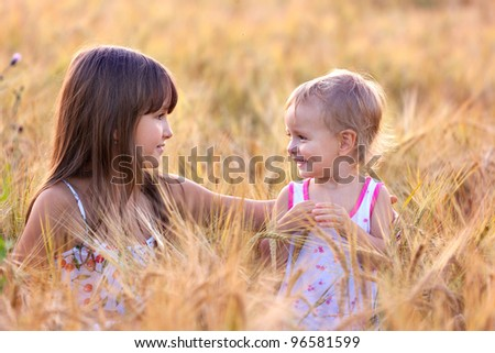 Two adorable sisters in the field of wheat - stock photo