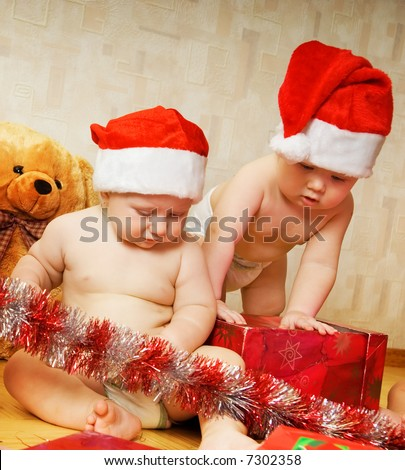 Two adorable toddlers in Christmas hats packing presents - stock photo