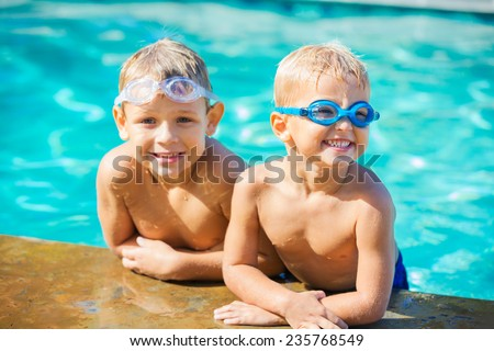 Two Adorable Young Boys Having fun at the Pool. Summer Vacation Fun.