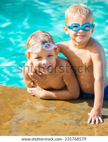 Two Adorable Young Boys Having fun at the Pool. Summer Vacation Fun.   - stock photo