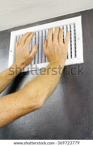 Two adult hands placed over an out air vent register of a central heating system on a gray wall near a white ceiling. A white metal air vent with two adult male caucasian hands on - stock photo