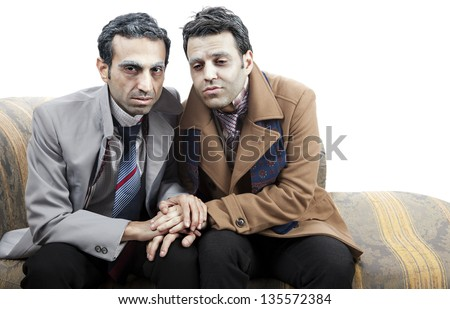 Two adult man (mid 30's and mid 20's) wearing old-man clothes and makeup, sitting on a used up vintage sofa. They both have quite a miserable and pitiful appearance. Isolated on white background.