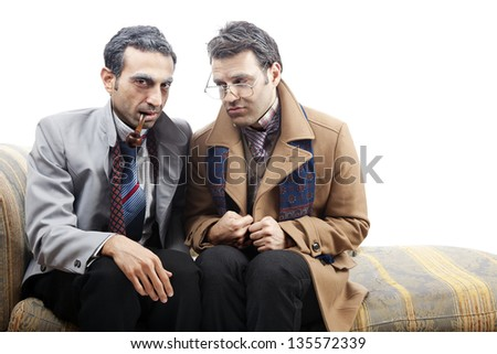 Two adult man wearing old-man clothes and makeup. One of them is looking at the camera with a pipe in his mouth while the other looking at him through his vintage glasses. Isolated on white background - stock photo