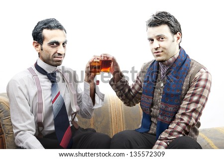 Two adult man wearing old-man clothes and makeup, sitting on a used up vintage sofa. Both of them are smiling at the camera while toasting their tea glasses. Isolated on white background. - stock photo
