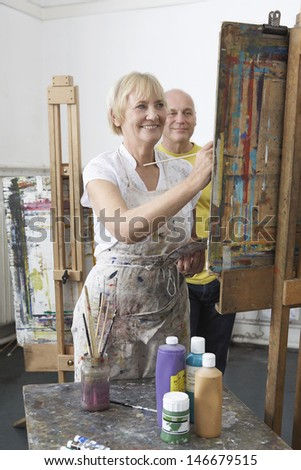 Two adult students painting at easel in art class - stock photo