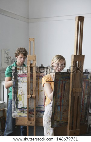Two adult students painting at easels in art class - stock photo