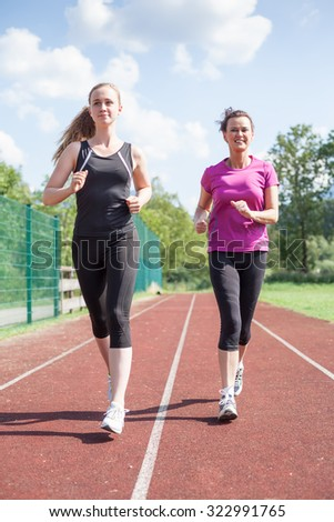 Two Adult Women Jogging Together in Separate Lanes on Outdoor Track - Full Length Front View of Positive Smiling Women Exercising Together