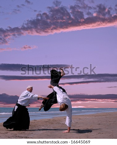 two adults are training in aikido on a beach - stock photo
